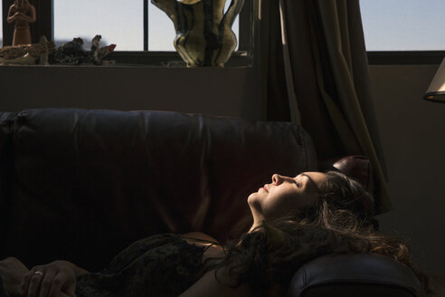 Side view of woman lying on sofa by window at home - CAVF47773