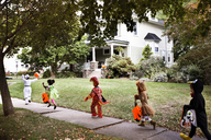 Children wearing Halloween costumes running on pathway towards house during trick or treating - CAVF47800