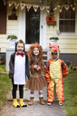 Portrait of smiling friends wearing Halloween costume standing in yard - CAVF47806