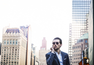 Businessman talking on phone while standing in city against clear sky - CAVF47815