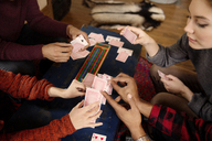 High angle view of friends stacking cards at table - CAVF47848
