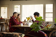 Friends talking while having coffee by window at home - CAVF47854
