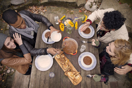 High angle view of friends having food at wooden table outdoors - CAVF47869