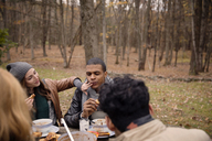 Couple having food with friends at table against trees - CAVF47872