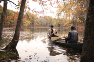 Friends rowing boat on lake amidst trees at forest - CAVF47875