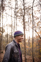 Smiling man standing against trees in forest during winter - CAVF47884
