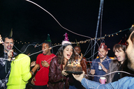 Happy friends enjoying with birthday cake in party at night - CAVF47896