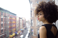 Thoughtful woman with curly hair looking through window in city - CAVF47911