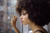 Close-up of thoughtful woman with curly hair looking through window - CAVF47917