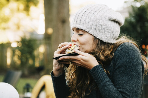 Woman eating sandwich while sitting in backyard - CAVF47972