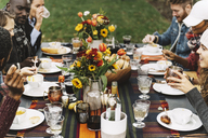 Friends eating food while sitting at table in backyard - CAVF48044