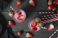 Glasses of strawberry smoothie and strawberries on dark wood - RTBF01204