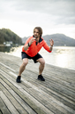 Athlete exercising on wooden deck at the lakeshore - DAWF00655