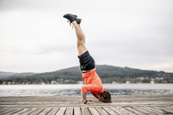 Athlete doing a headstand on wooden deck at the lakeshore - DAWF00658