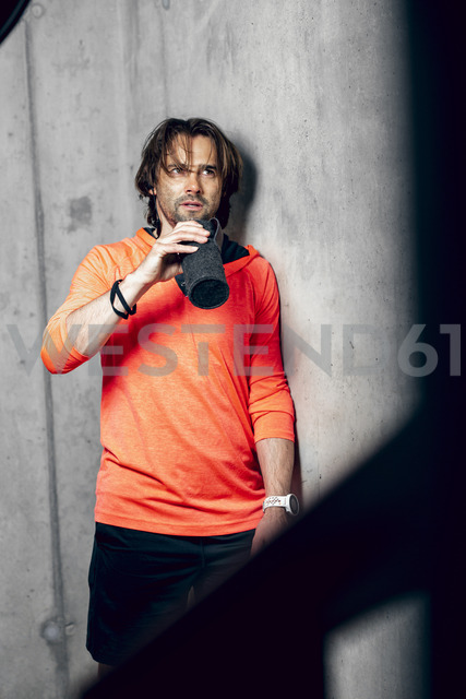 Athlete wearing standing at concrete wall drinking from flask - DAWF00661