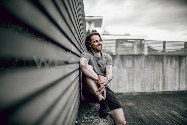 Smiling athlete sitting outdoors having a break - DAWF00673