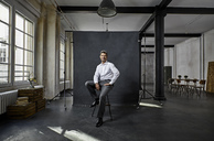 Portrait of mature businessman in front of black backdrop in loft - PDF01564