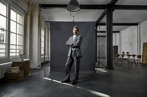 Portrait of mature businessman in front of black backdrop in loft - PDF01567