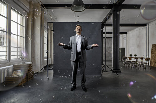 Mature businessman with bubbles standing in front of black backdrop in loft - PDF01570