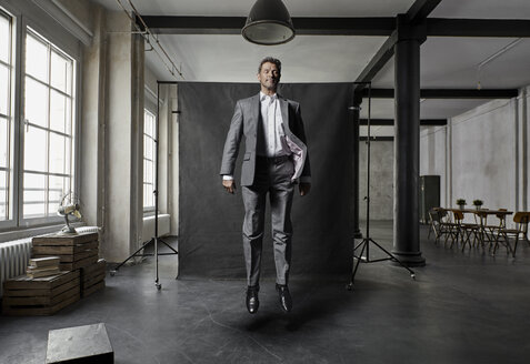 Mature businessman floating in front of black backdrop in loft - PDF01573