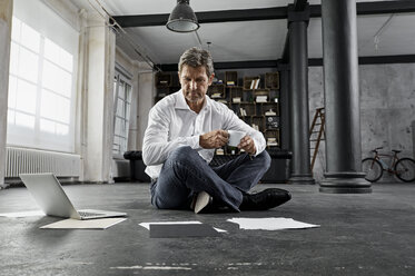 Mature man sitting on ground with laptop and notes in loft - PDF01582