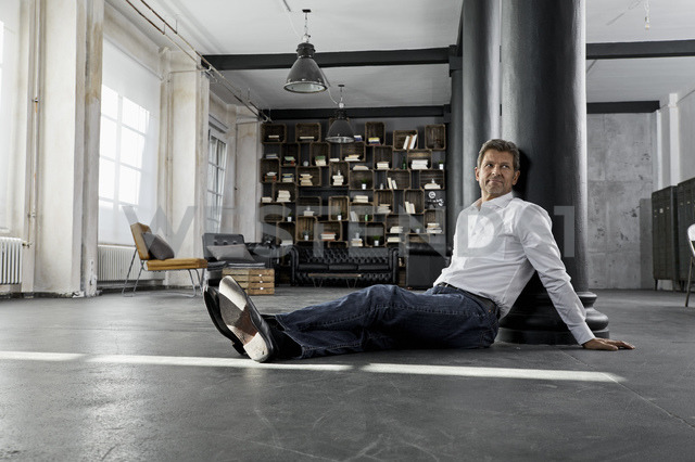 Mature man sitting on the floor in loft flat - PDF01585
