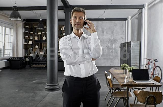 Portrait of mature business man using smartphone in loft office - PDF01588