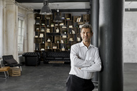 Portrait of mature man in loft leaning against a column - PDF01591