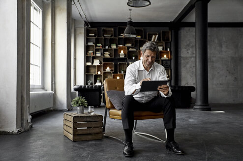 Smiling mature man using digital tablet in loft - PDF01603