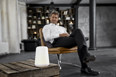Mature man using voice-controlled digital assistant in loft - PDF01606