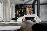 Smiling mature man using digital tablet in loft office - PDF01612