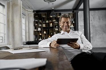 Smiling mature man using digital tablet in loft office - PDF01612