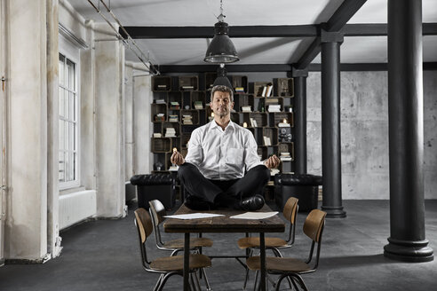 Portrait of mature businessman doing yoga on desk in loft office - PDF01615