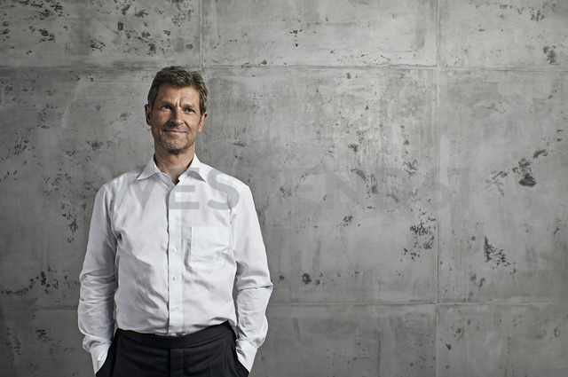Portrait of smiling mature man in front of concrete wall - PDF01618