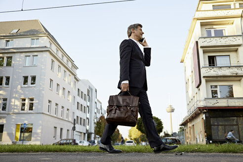 Mature businessman walking and using smartphone in the city - PDF01624