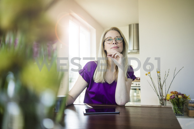 Portrait of pensive woman sitting at  table at home - MOEF01039