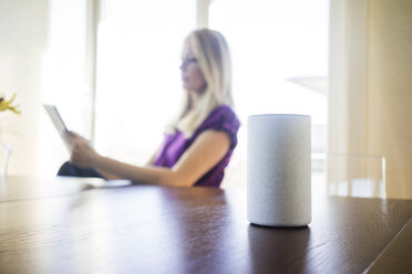 Smart Home loudspeaker on table with woman using tablet in the background - MOEF01048
