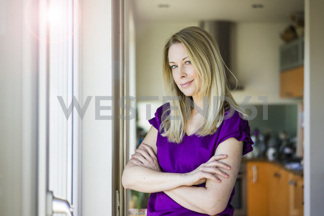 Portrait of smiling blond mature woman at home - MOEF01051