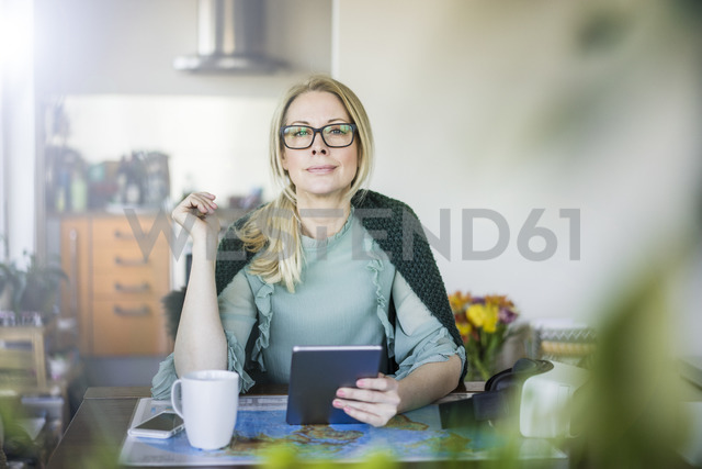 Portrait of blond businesswoman with tablet and world map - MOEF01060