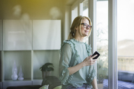 Portrait of content woman with smartphone looking out of window - MOEF01063