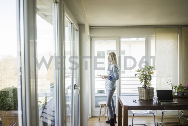 Woman with tablet looking out of window - MOEF01069