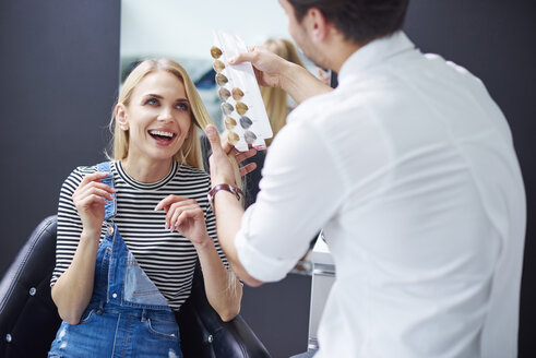 Hairdresser and happy woman at hair salon - ABIF00341