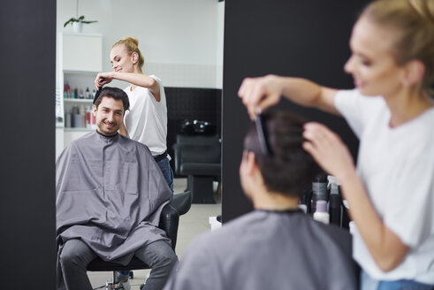 Smiling hairdresser combing man's hair - ABIF00350