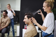Smiling hairdresser using hairspray on man's hair - ABIF00353