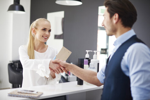 Hairdresser and smiling woman shaking hands in hair salon - ABIF00362