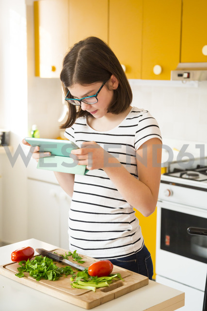 Girl standing in the kitchen using tablet - LVF06895
