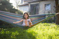 Portrait of smiling little girl sitting on hammock in the garden - LVF06903