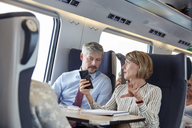 Business people working, using smart phone and talking on passenger train - CAIF20253