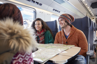 Smiling young friends planning with map on passenger train - CAIF20256