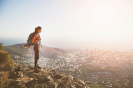Female rock climber on top of hill overlooking sunny city - CAIF20280